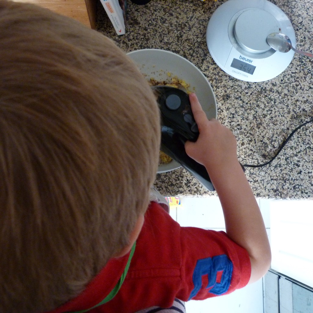 overhead shot of child baking with hand mixer