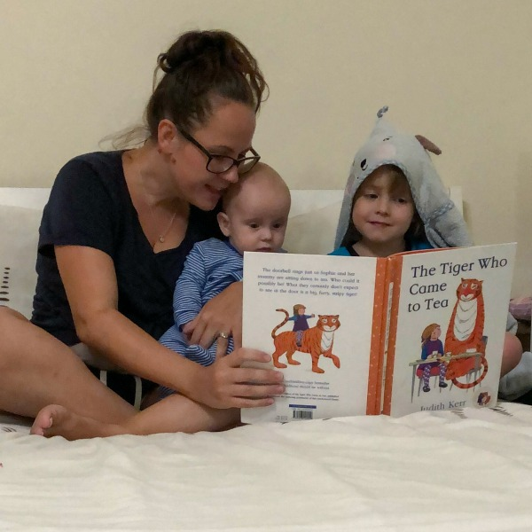 mum reading a story to two children