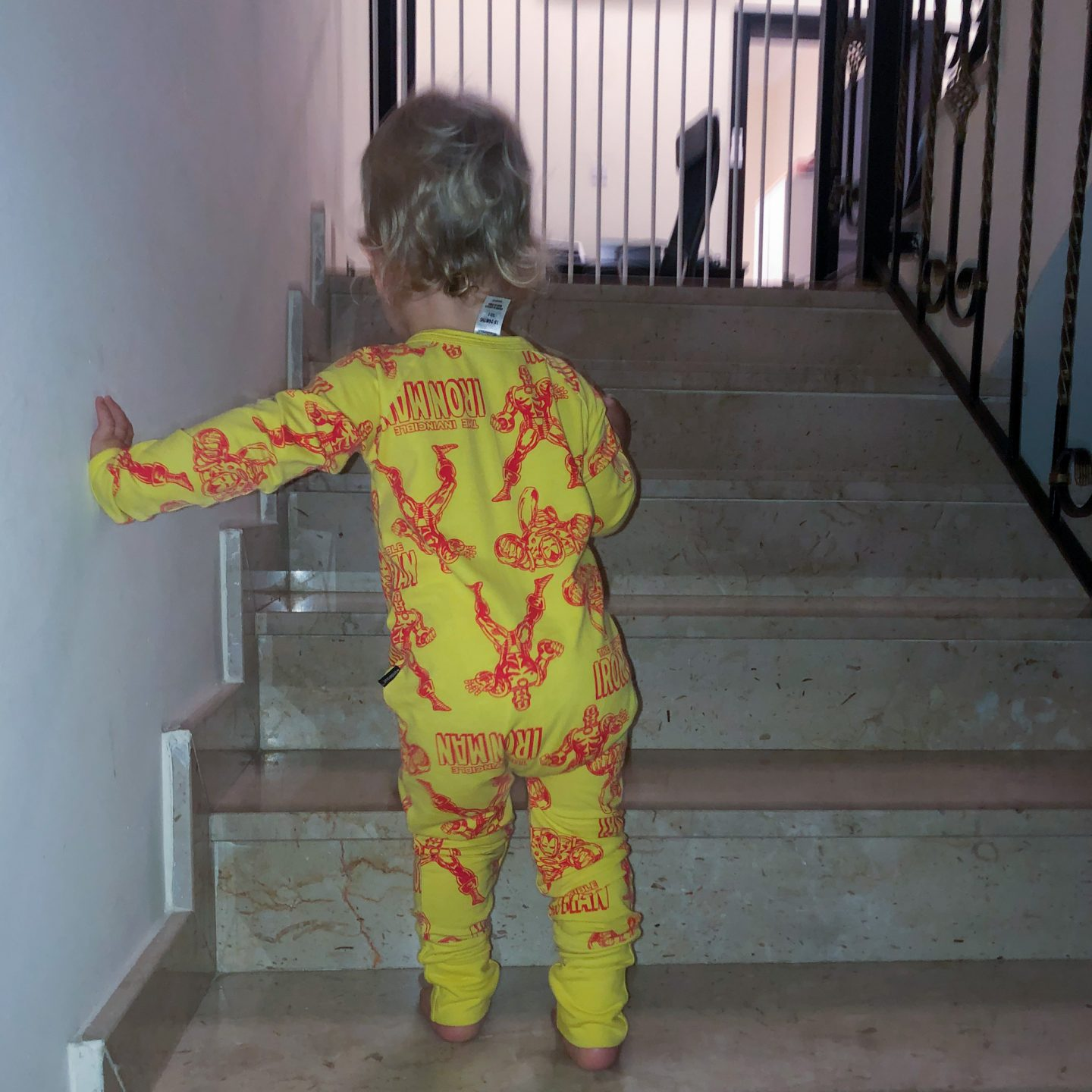 Baby walking up the stairs to bed wearing Ironman babygrow