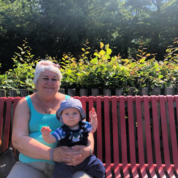 Grandmother sitting with 6 month old grandson on red bench