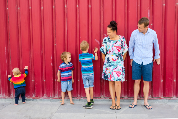 family of five, mum, dad, three boys, against red wall background