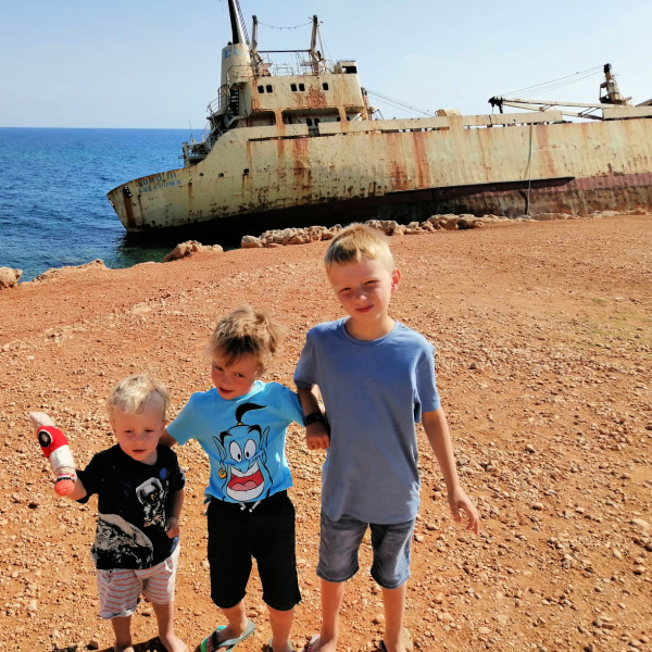 Three boys in front of shipwreck Cyprus